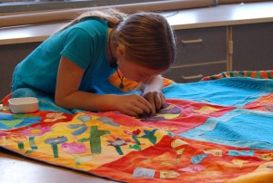 child working on story quilt